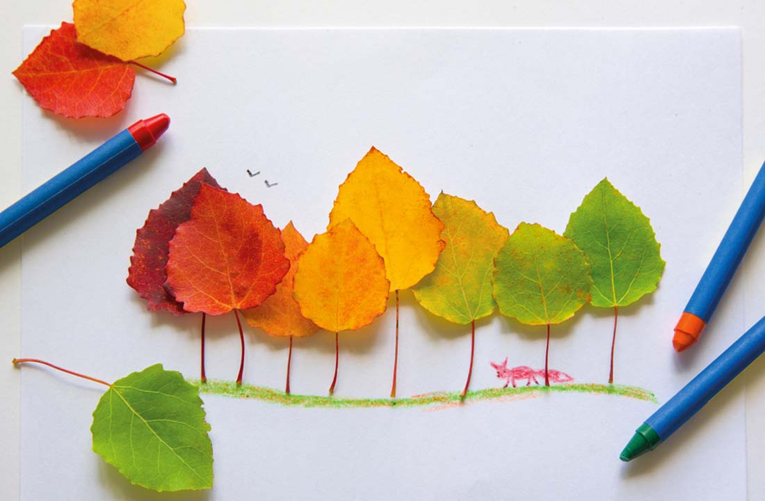 Autumn leaves stuck to make trees in artwork with crayons