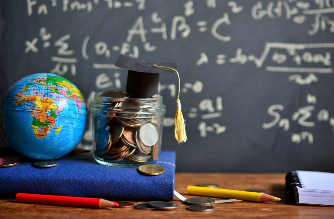 A little jar of coins on a notebook next to a little globe, pencils and coins scattered on the desk against a backdrop of a blackboard with maths equations