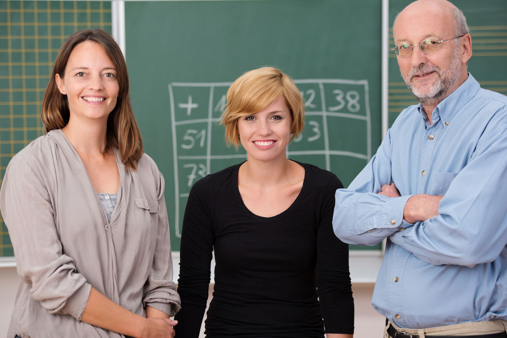 teachers in front of blackboard 1000px - How Do Agencies Generate Work for Supply Teachers?